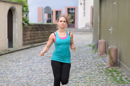 approaching: Attractive athletic young woman jogging in town running down a narrow cobbled street during a workout or training session