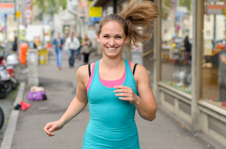 upper body: Happy energetic young woman jogging through town with her ponytail flying out behind her and a friendly smile on her face, close up upper body on a busy street