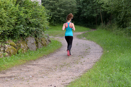 sleeveless top: Young healthy fit woman with blond long hair wearing green sleeveless top and black leggings and jogging outdoors on an alley of a green forested area
