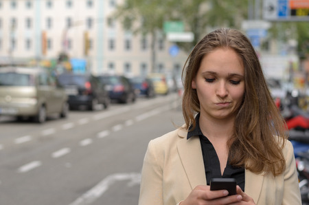 dubious: Young woman reading a text message on her mobile grimacing a pulling a dubious expression as she reads the text in an urban street, closeup head and shoulders