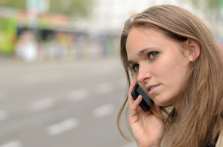 woman outdoor: Thoughtful young woman talking on her mobile standing on an urban street looking aside with a serious expression , closeup profile view of her face Stock Photo