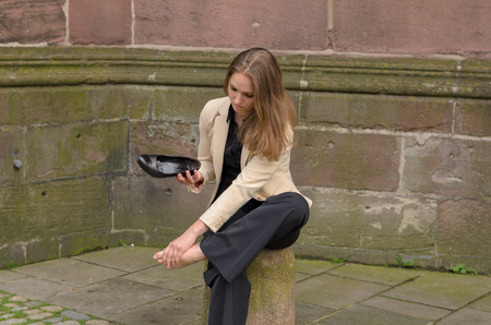 by feet: Stylish young woman with aching feet pausing in town to sit on a cement bollard as she removes her high heels to massage her foot