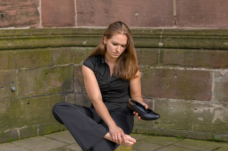 Stylish young woman with aching feet pausing in town to sit on a cement bollard as she removes her high heels to massage her foot
