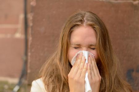 gripa: Mujer joven que sopla su nariz en un pañuelo conceptual de una enfermedad, gripe, rinitis alérgica o fiebre del heno frío Foto de archivo