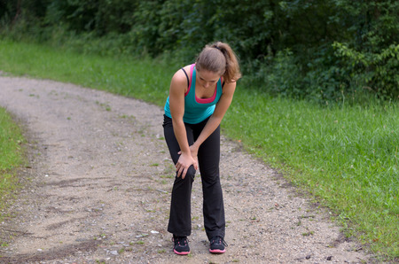 on hands and knees: Athletic young woman with a knee injury pausing during her training running along a rural dirt track to clasp her knee in her hands