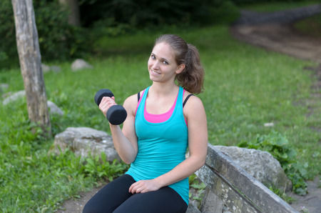 body toning: Fit young woman working out with a dumbbell as she sits on a rustic wooden bench in a park flexing her arm to strengthen her muscles