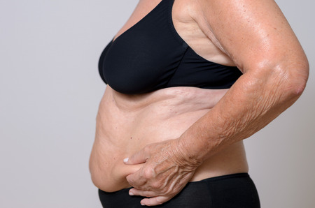 midriff: Elderly overweight lady pinching her excess fat at the side of her stomach between her fingers as she poses in profile in her bra and panties, close up midriff view on grey Stock Photo