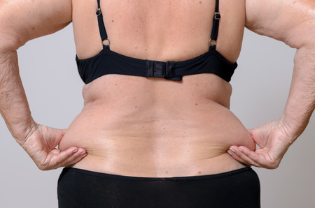 bragas: Mujer mayor apretando su exceso de grasa sobre sus caderas en la parte posterior entre sus dedos mientras posa en sus bragas y sujetador, opinión del torso