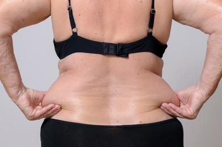 femme en sous vetements: Senior femme serrant son exc�s de graisse sur les hanches � l'arri�re entre ses doigts comme elle pose dans sa culotte et soutien-gorge, vue rapproch�e du torse Banque d'images