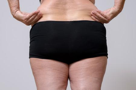 Close-up Rear View van een volwassen vrouw in zwart ondergoed bedrijf haar dikke buik tegen hemelsblauwe achtergrond. Stockfoto