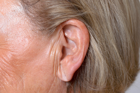 lobe: Close up of the ear of an elderly woman with her blond ear tucked back behind the ear to expose the lobe