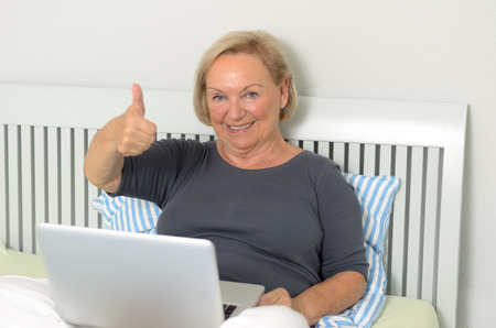 oldage: Senior woman giving a thumbs up gesture of approval as she relaxes cross-legged on her bed with her laptop computer surfing the internet