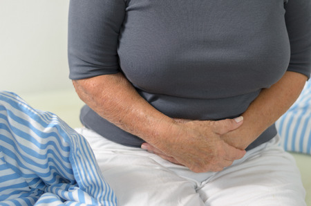diarrhoea: Woman with stomach ache clutching her stomach with clasped hands as she sits on the edge of her bed in her clothes, close up of her hands