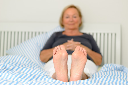 women undressing: View of the soles and bare feet of a woman relaxing on her bed with selective focus to the soles and a toe to head perspective Stock Photo