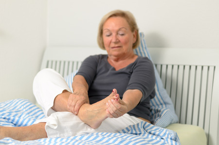 senior pain: Senior lady massaging her bare foot to relive aches and pains as she sits relaxing against the pillows on her bed Stock Photo