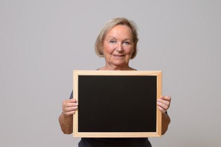 femme blonde: Happy senior woman avec des cheveux blonds montrant un petit tableau noir vierge tout en souriant � la cam�ra, portrait, avec copie espace sur fond gris