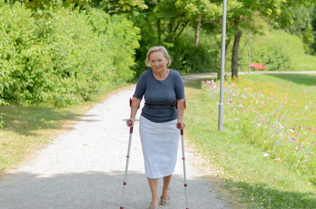 coping: Elderly lady walking in the country along a rural lane on crutches as she tries to exercise and stay fit despite a handicap or injury Stock Photo