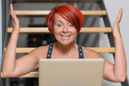animated women: Close up Happy Middle Aged Redhead Woman with Laptop Computer, Sitting on the Stairs and Raising her Arms for Success.