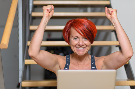 exuberant: Close up Happy Middle Aged Redhead Woman with Laptop Computer, Sitting on the Stairs and Raising her Arms for Success.