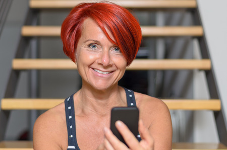 socialising: Close up Pretty Face of an Adult Redhead Woman Texting on Mobile Phone and Smiling at the Camera Against Blurry Stairs. Stock Photo