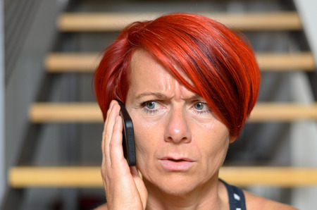 perturbed: Close up Serious Redhead Adult Woman Calling Someone on her Mobile Phone While looking Into the Distance.