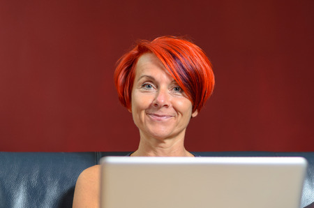 pert: Close up Pretty Adult Woman with Red Orange Hairstyle, Sitting on the Sofa with her Laptop Computer and Smiling at Camera Against Brown Wall.