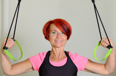 muscle toning: Close up Sporty Adult Redhead Woman Looking Straight at the Camera While Pulling Down a Resistance Band to Tone her Arm Muscles Against White Wall.