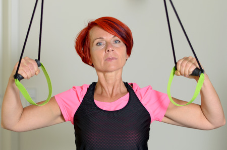 body toning: Close up Sporty Adult Redhead Woman Looking Straight at the Camera While Pulling Down a Resistance Band to Tone her Arm Muscles Against White Wall.