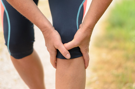 on hands and knees: Close up Athletic Woman Holding her Painful Injured Knee While Doing an Outdoor Exercise. Stock Photo