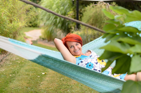 contented: Happy Middle Aged Redhead Woman Smiling at the Camera While Relaxing on Hammock at the Garden