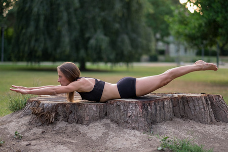 outspread: Athletic woman in summer shorts in an artistic pose on an old tree stump with the glow of the sunrise or sunset behind her head in a park Stock Photo