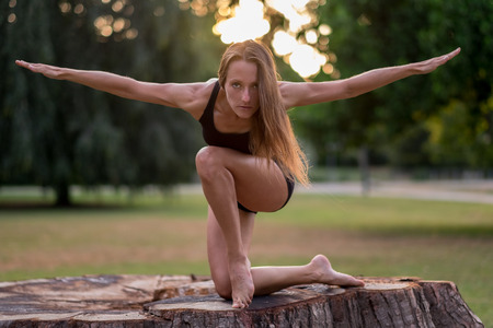 human arm: Athletic woman in summer shorts in an artistic pose on an old tree stump with the glow of the sunrise or sunset behind her head in a park Stock Photo