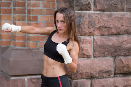 pugilist: Young female boxer with her hands bandaged working out at a training session at a gym throwing a punch and looking at the camera with a serious determined expression
