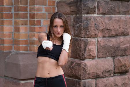 pugilist: Boxeadora joven con sus manos vendadas que se resuelve en una sesi�n de entrenamiento en un gimnasio lanzando un pu�etazo y mirando a la c�mara con una determinada expresi�n seria Foto de archivo