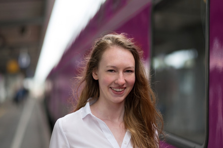 Smiling attractive young woman standing on a train station platform alongside a stationary train as she prepares to board for a trip or commute Stock Photo
