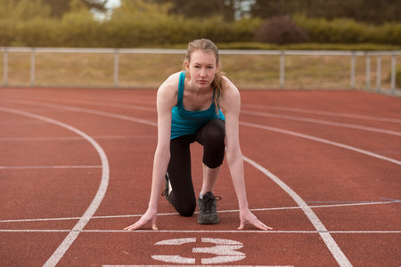 downloaded: Young woman sprinter in the starter position on a race track at a sports stadium looking up at the camera with determination