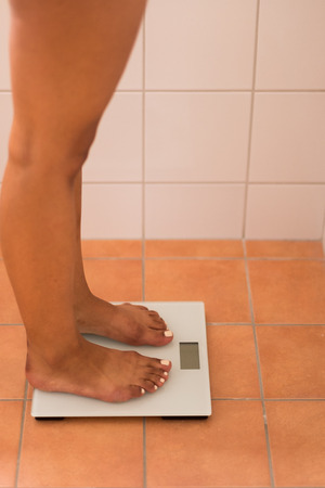 readout: Close up Bare Legs of a Woman Checking her Weight Using a Digital Weighing Scale at Home. Stock Photo