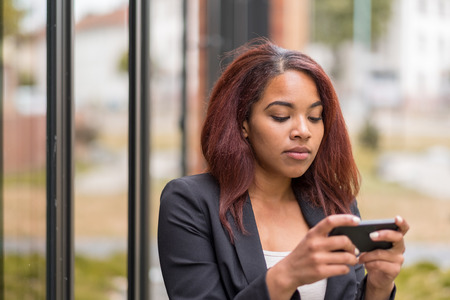 Close up Young African-American Office Woman Texting to Someone Using her Mobile Phone with Serious Facial Expression. Foto de archivo