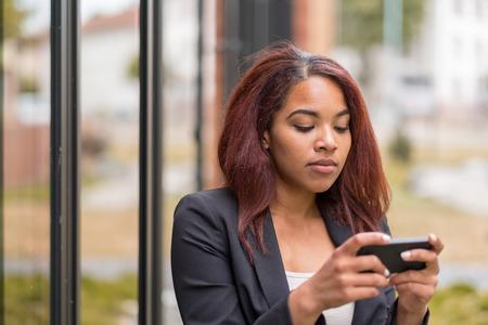 pretty woman: Cierre de joven afroamericano-oficina de la mujer Texting alguien que usa su tel�fono m�vil con la expresi�n facial seria.