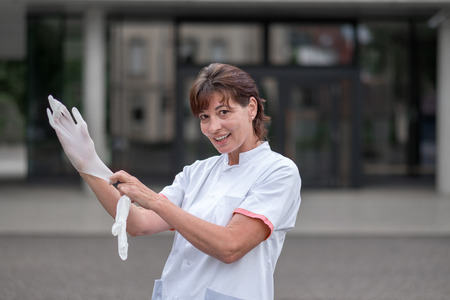 nurse gloves: Female doctor or nurse standing outdoors in front of a hospital putting on latex gloves for protection or sterility as she prepares to do an examination