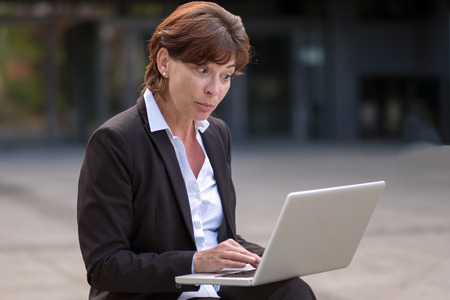 dubious: Businesswoman receiving a surprise as she reads information on her laptop computer looking at the screen with a wide-eyed speculative expression, seated outdoors Stock Photo