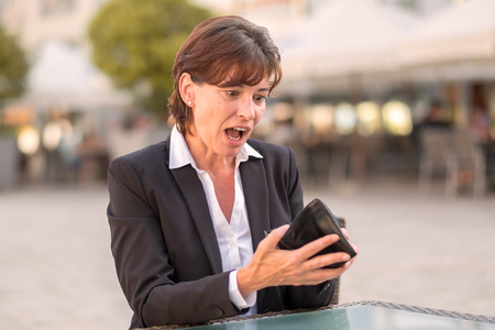 horrified: Horrified woman unable to pay her bill at a street cafeteria as she realises that her wallet is empty and she does not have her credit card Stock Photo