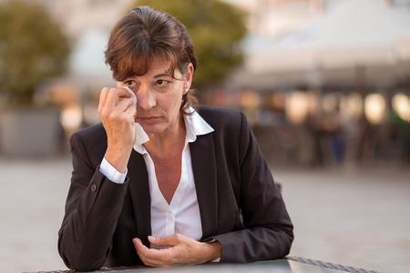 lagrimas: Mujer llorosa sentada al aire libre en una mesa en una calle urbana llorando y secándose los ojos con un pañuelo