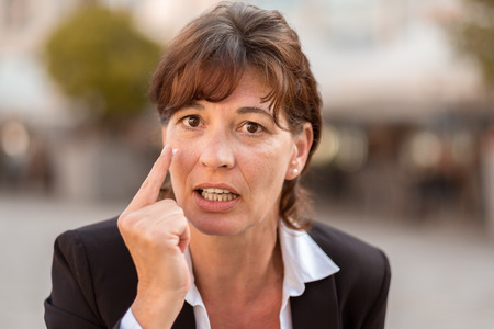 emphatic: Close up Angry Middle Aged Businesswoman Pointing her Finger and Looking at the Camera. Stock Photo