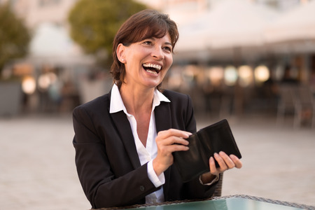 vivacious: Laughing vivacious attractive woman sitting at an outdoor urban restaurant making a payment reaching inside her wallet for money or a credit card