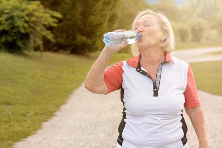 sediento: Mujer mayor sana beber agua embotellada que se toma un descanso mientras que hacia fuera que activa en un camino rural en un concepto de salud y estado físico