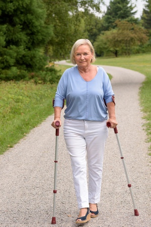 recuperation: Full Length Shot of a Middle Aged Woman Walking on the Pathway with Two Canes and Smiling at the Camera. Stock Photo