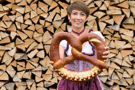 neatly stacked: Smiling young Bavarian woman wearing a traditional dirndl dress stnding in front of a neatly stacked woodpile holding a large decorative knotted pretzel in her hands