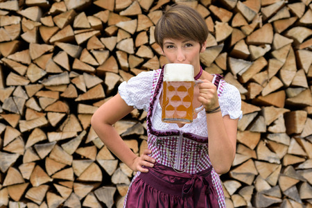 tankard: Young woman in a traditional Bavarian dirndl standing in front of a neat woodpile drinking a cold beer from a large glass tankard conceptual of the Oktoberfest