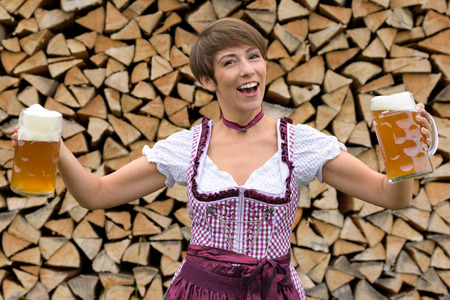 vivacious: Vivacious woman in a dirndl holding two beers in glass tankards in her hands as she toasts the Oktoberfest, stacked woodpile background Stock Photo